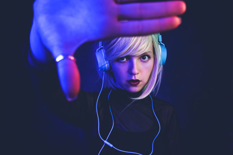 Headphones Listening One Person Technology Music Portrait Indoors  Lifestyles Blue Real People Looking At Camera Front View Leisure Activity Headshot Arts Culture And Entertainment Holding Studio Shot Close-up Black Background Dj Futuristic Party Art Duotone