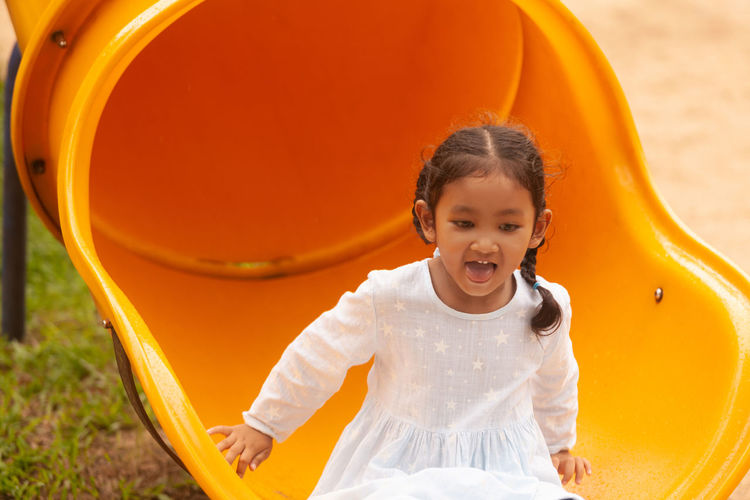 Cute girl having fun while sliding in playground