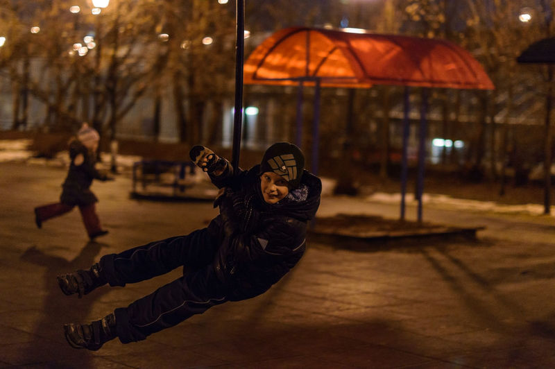 Full length portrait of boy swinging in city at night during winter