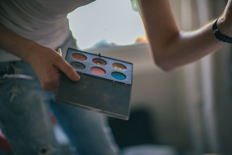 Midsection of make-up artist holding palette