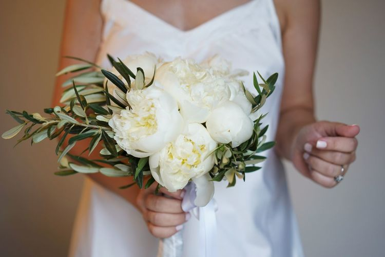 Midsection of bride woman holding wedding flower bouquet