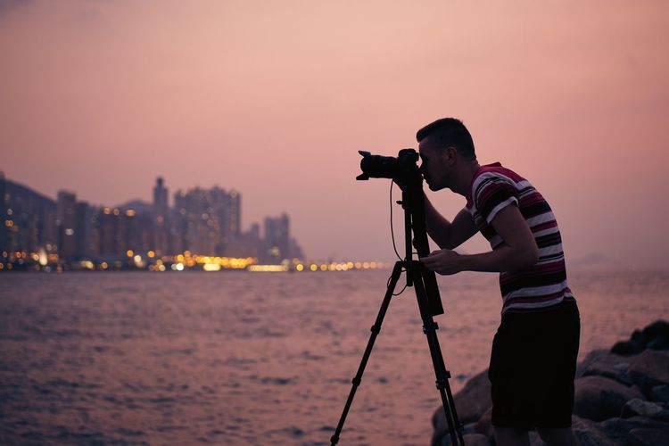 Man photographing at camera against sky during sunset