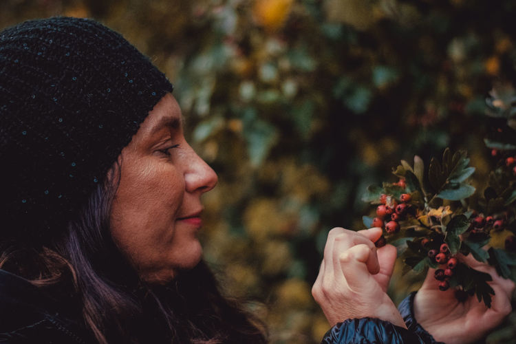 Portrait of woman holding red flower