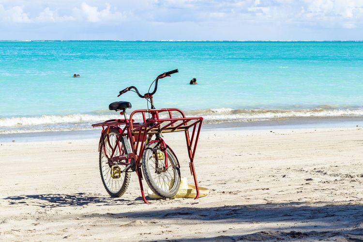 Bicycle parked at beach against sky