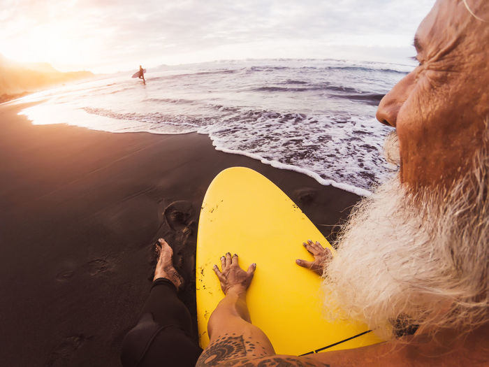 Close-up of senior man with surfboard sitting at beach