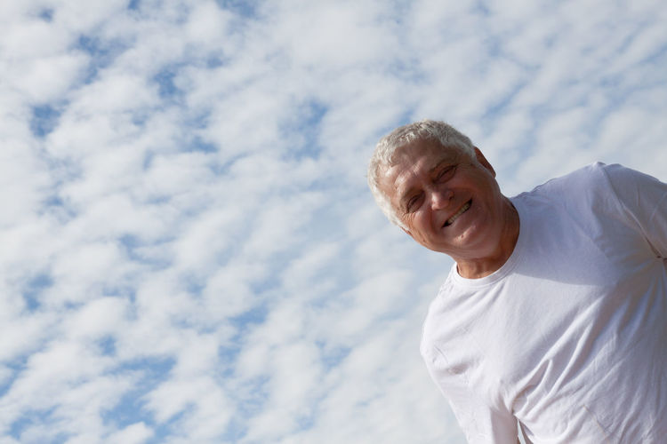 Low angle portrait of mature man against cloudy sky