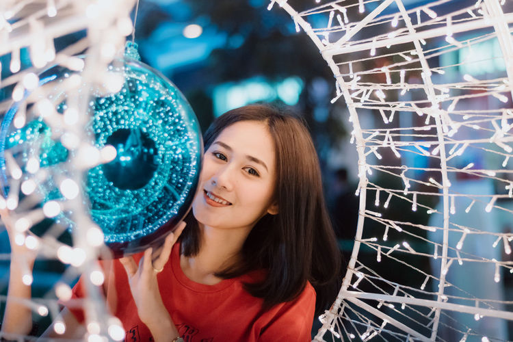 Merry Christmas. Christmas Christmas Lights Christmas Decoration Christmas Ornament Christmas Themes One Person Leisure Activity Portrait Smiling Young Women Headshot Women Illuminated Indoors  Front View Emotion Happiness Adult Lifestyles Young Adult Real People Looking At Camera Casual Clothing Decoration Hairstyle Nightlife Beautiful Woman