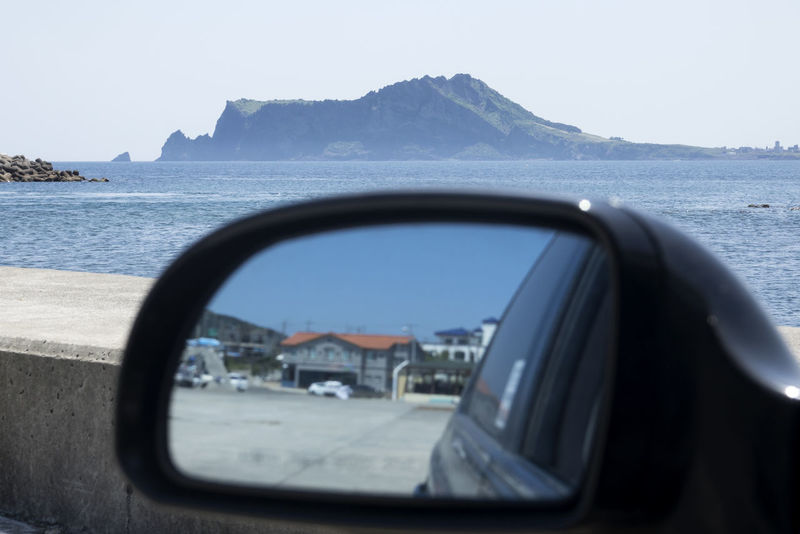 Seongsan Ilchulbong and mirror view in Udo Island, Jeju, South Korea JEJU ISLAND  Beauty In Nature Car Clear Sky Close-up Day Land Vehicle Mode Of Transport Mountain Mountain Range Nature No People Outdoors Reflection Sea Seongsan Ilchulbong Side-view Mirror Sky Transportation Udo Vehicle Mirror Water