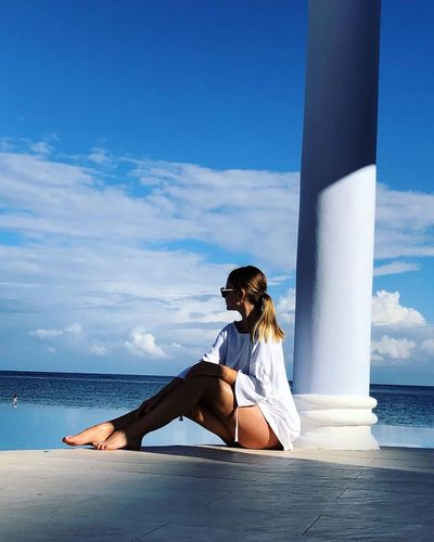 Young woman sitting by column while looking at sea against sky