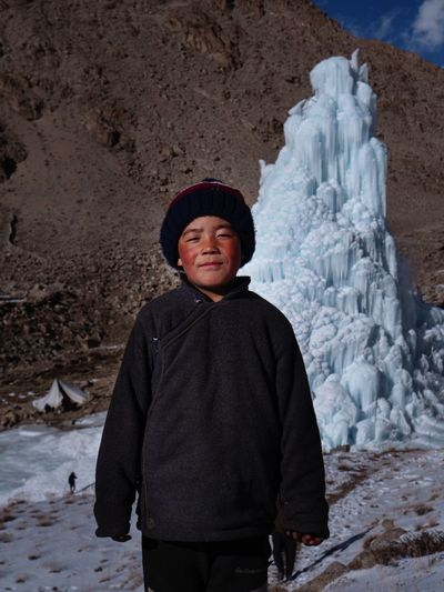 Boy standing on snow covered land