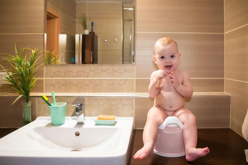 Portrait of cute baby boy in bathroom at home