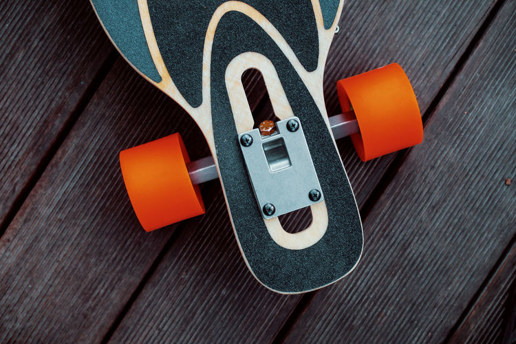FOR FUN Skateboarding Skateboard No People Close-up Wood - Material Orange Color Safety Equipment Still Life Security Metal Wheels Indoors  Scissors High Angle View Protection Group Of Objects Two Objects Studio Shot Shadow Wood Single Object Silver Colored