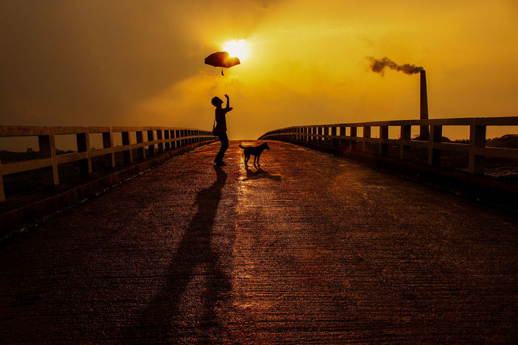 Man walking on bridge against sky during sunset