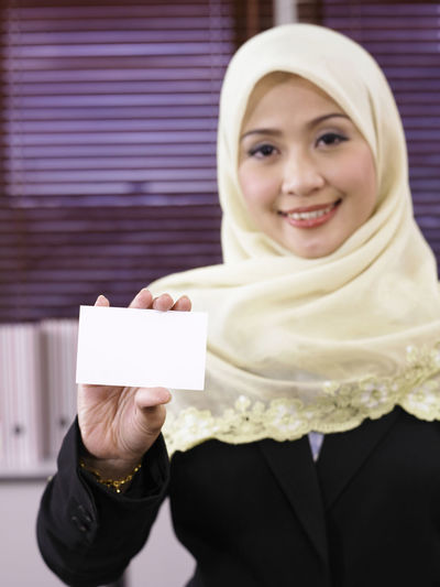 Portrait Of Businesswoman In Hijab Showing Blank Business Card At Office