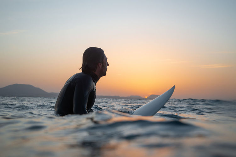 Sunset Sea Water Sky Real People One Person Beauty In Nature Leisure Activity Lifestyles Nature Men Scenics - Nature Young Adult Waterfront Side View Adult Young Men Tranquility Outdoors Horizon Over Water