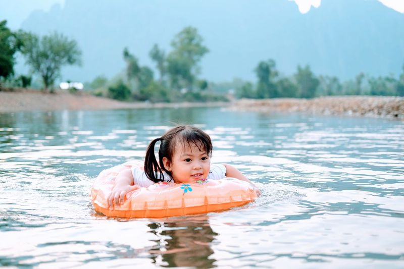 Portrait of girl in swimming with tube at river