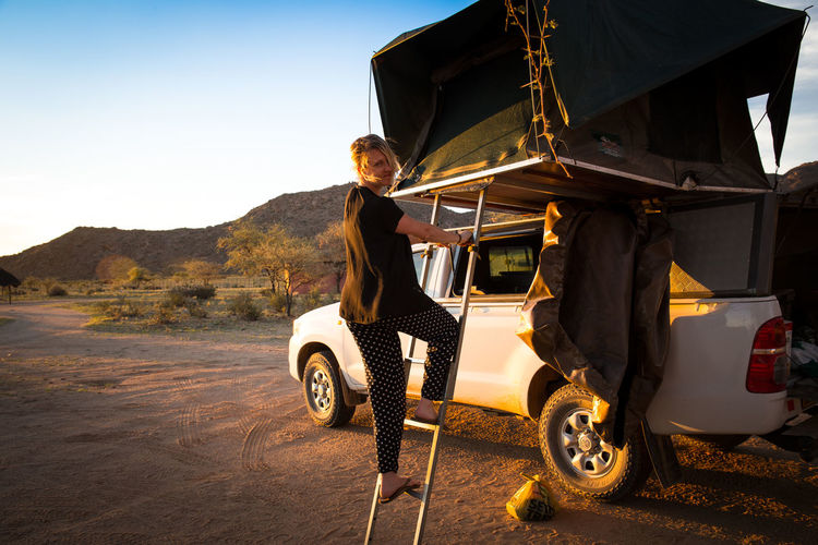 Portrait Of Woman Standing On Tent Ladder By Pick-Up Truck At Desert