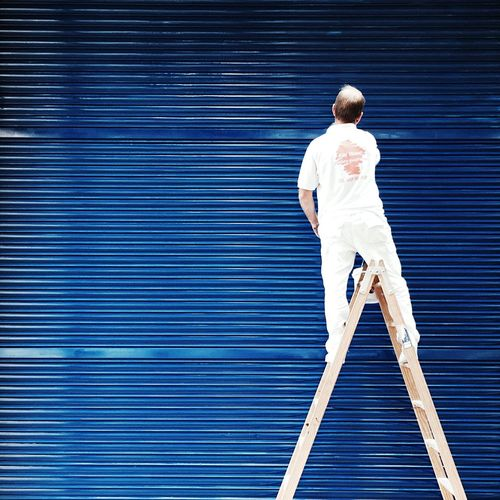 Rear view of man standing on ladder against blue corrugated iron
