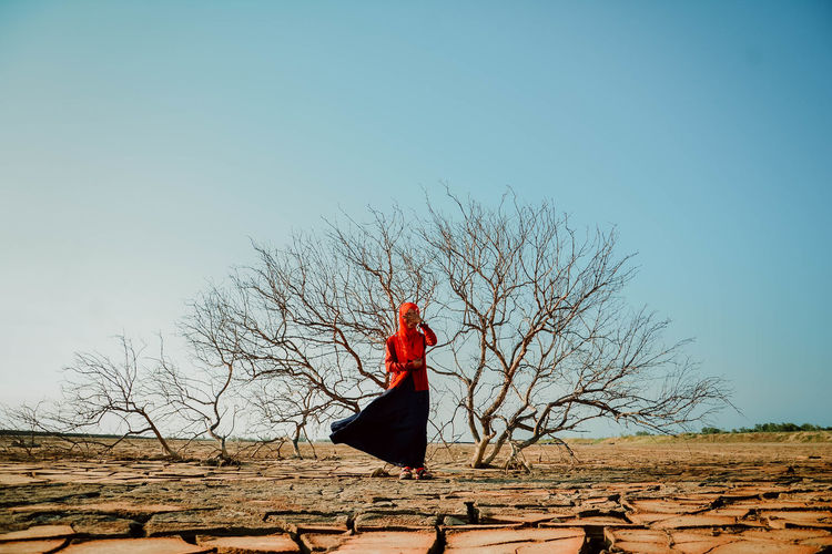 Young woman standing against bare tree on cracked field