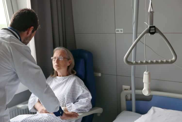 Doctor With Senior Woman In Examination Room