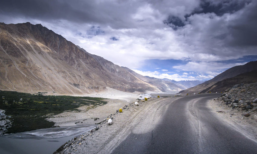 Empty Road By Majestic Mountains Against Cloudy Sky