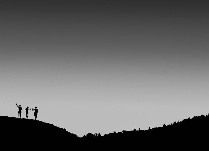 Silhouette people standing on land against sky