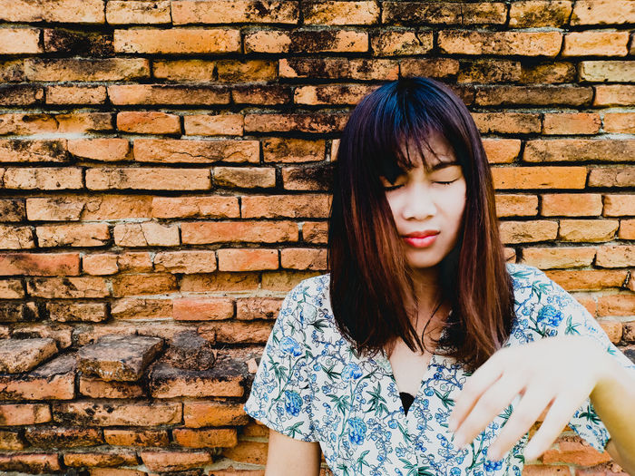 Young woman with closed eyes against brick wall
