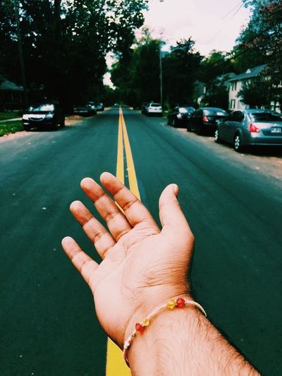Cropped image of hand with street in background