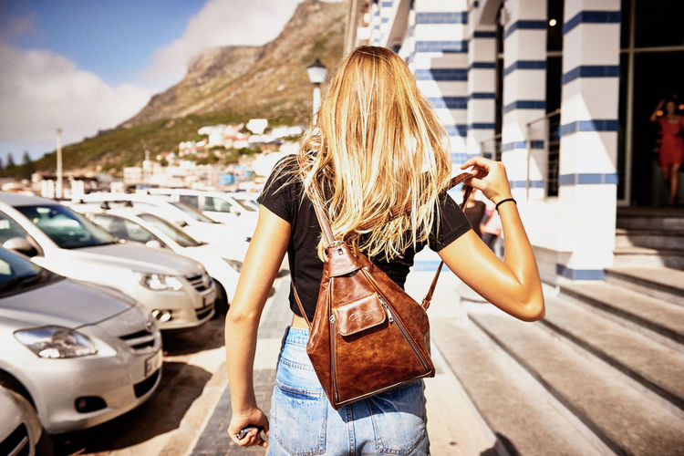Rear View Of Woman Wearing Backpack While Walking By Parked Cars