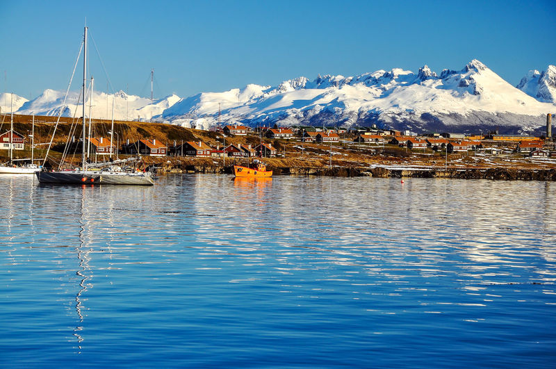 Boats moored in sea by town against snowcapped mountains