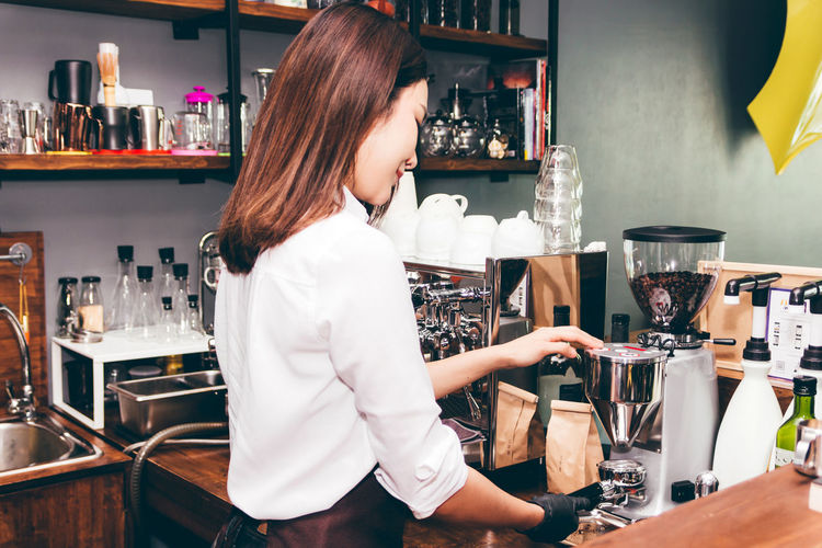 Women Barista using coffee machine for making coffee in the cafe Adult Alcohol Bar - Drink Establishment Bar Counter Bartender Business Drink Food Food And Drink Freshness Glass Hairstyle Indoors  Lifestyles Occupation One Person Real People Refreshment Restaurant Standing Women Working