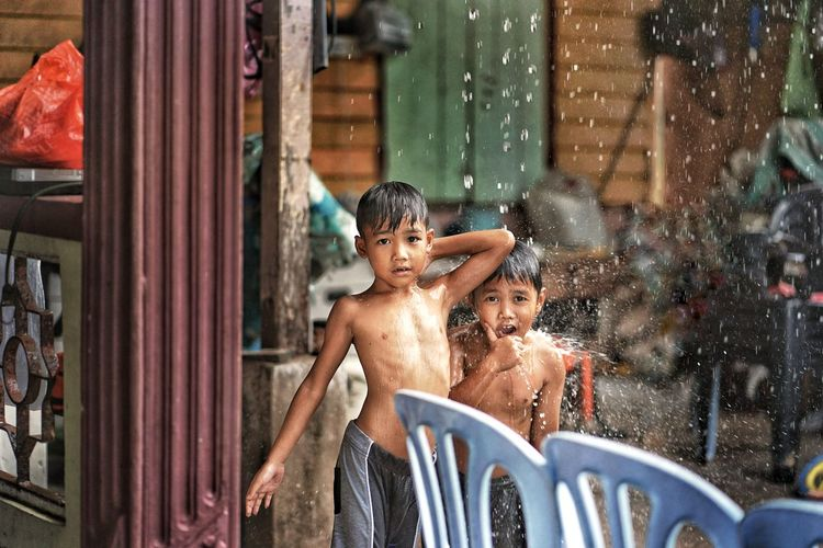 Kids playing out in the rain. children play outdoors in heavy rain, caught in first spring rainy day