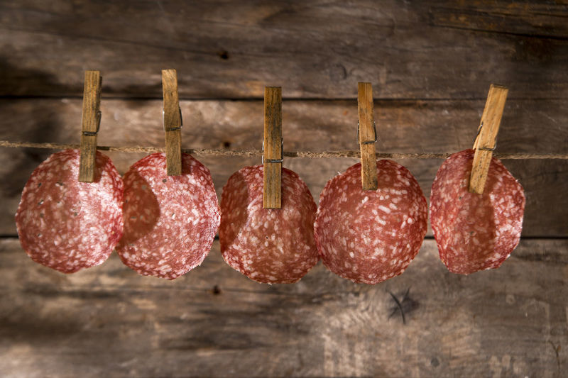 Close-Up Of Bacons Hanging On Clothesline Against Wood