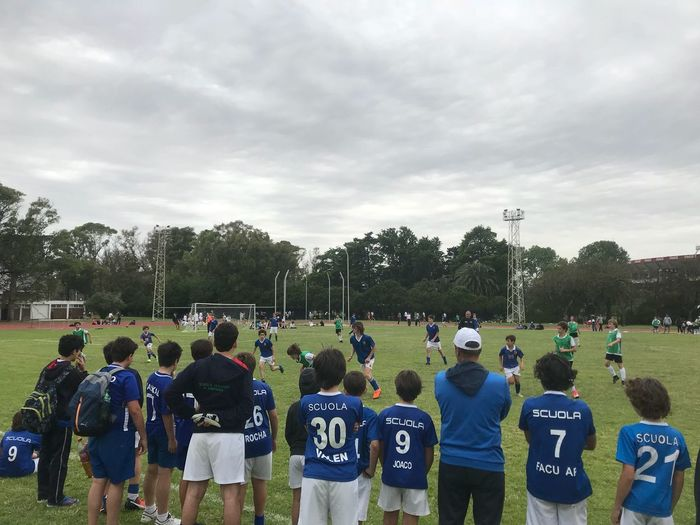 Soccer match Soccer Match Group Of People Real People Sky Large Group Of People Crowd Cloud - Sky Tree Plant Clothing Day Nature Men Sport Side By Side Teamwork Cooperation Outdoors Rear View Sports Clothing Uniform