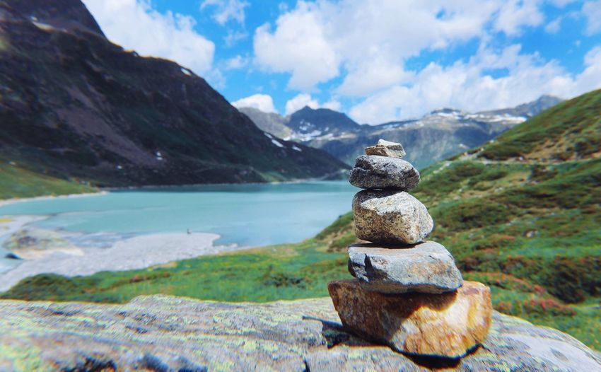 Stack of pebbles on mountain against sky