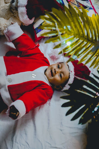High angle view of baby boy wearing santa hat while lying on bed