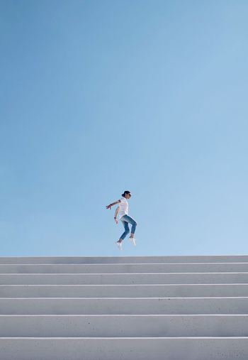 Low angle view of person jumping against clear sky