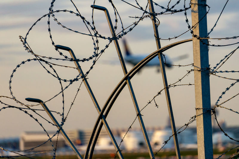 Fence Barrier Boundary Safety Metal Security Protection Focus On Foreground Razor Wire No People Barbed Wire Wire Day Selective Focus Sunset Outdoors Close-up Sharp Airport Air Vehicle Airplane