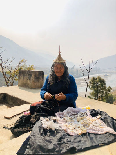 Portrait of old tribal woman sitting on rock against sky