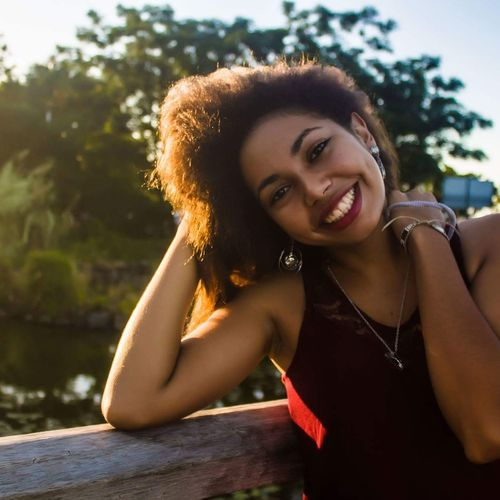 Portrait of smiling young woman standing by wooden railing at park