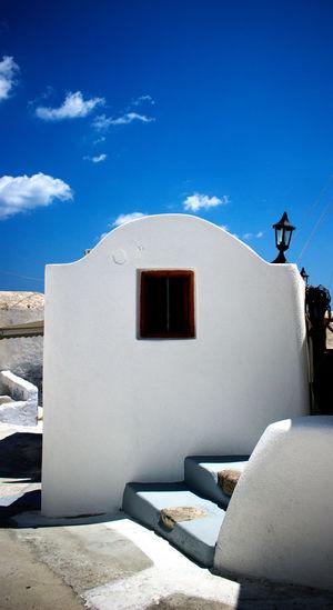 Whitewashed building at santorini against blue sky