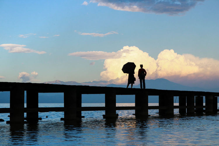 Silhouette people standing on pier over lake against sky