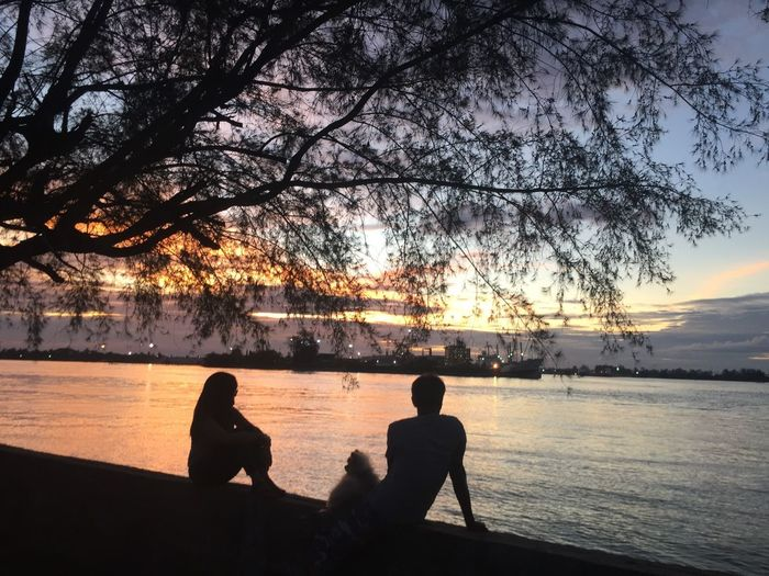 Silhouette people sitting on shore against sky during sunset