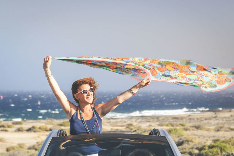 Summer vacation and travel concept image of a young woman waving headscarf out of hood of convertible car. Curly brunette girl arms up, having fun in a cabriolet topless. Female enjoying freedom One Person Leisure Activity Young Adult Lifestyles Real People Happiness Front View Emotion Young Women Smiling Car Sky Motor Vehicle Nature Transportation Human Arm Mode Of Transportation Day Arms Raised Outdoors Wind