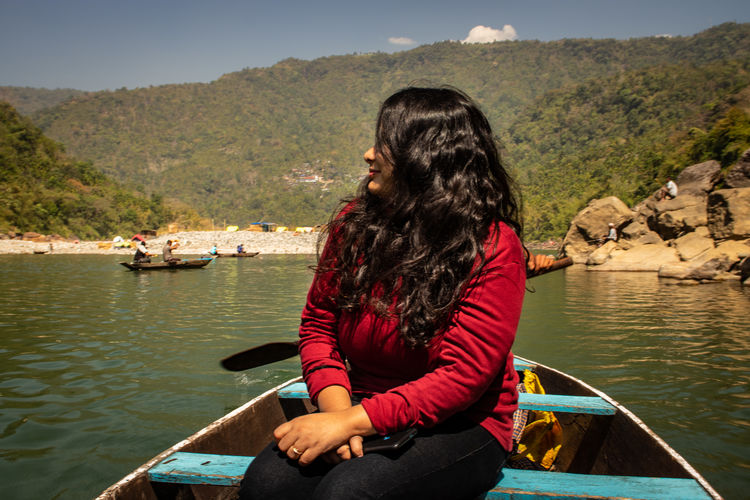 Woman sitting in boat against mountains