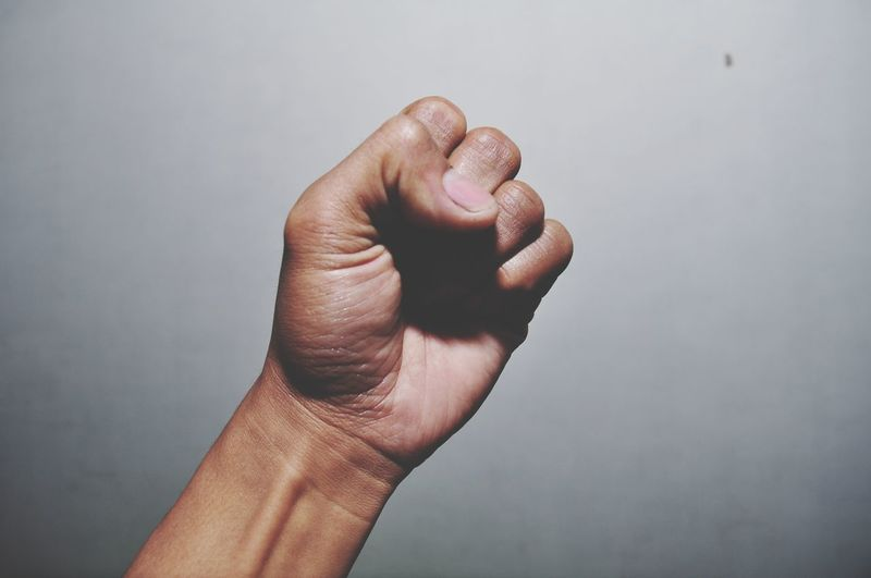Cropped hand of man gesturing fist against gray background
