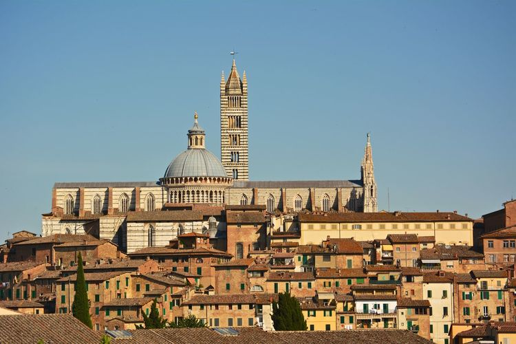 Buildings and duomo di siena against blue sky