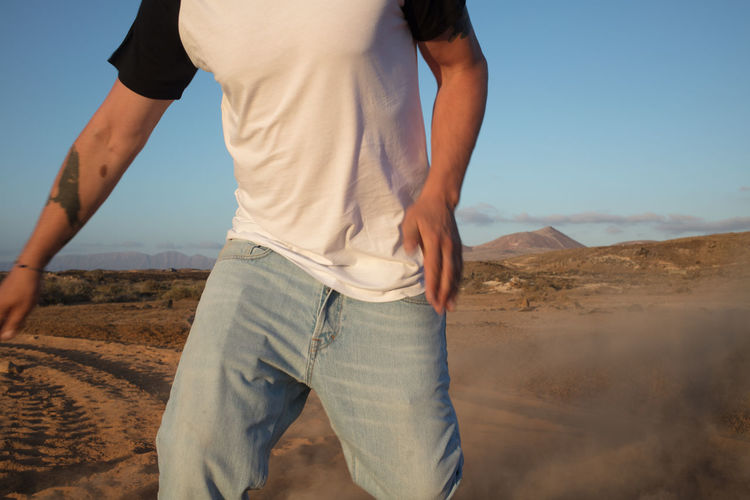 Midsection of man standing on desert land