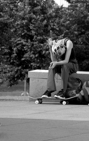 Rear view of man sitting on skateboard park