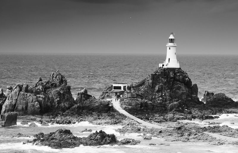 La Corbiere lighthouse, Jersey, Channel Island, United Kingdom Sea Guidance Water Lighthouse Tower Building Exterior Sky Built Structure Architecture Building Nature Scenics - Nature Land Horizon Over Water Beach Rock Beauty In Nature Direction Safety Outdoors Rocky Coastline Corbiere Jersey Channel Island UK Black And White Monochrome Copy Space Uk